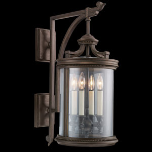 Louvre Four-Light Outdoor Wall Mount in Bronze Finish and Features Clear Hand Blown Glass and Antiqued Candles