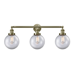Beacon Antique Brass Three-Light LED Bath Vanity with Eight-Inch Clear Globe Glass