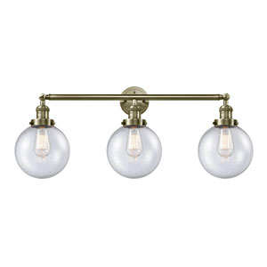 Beacon Antique Brass Three-Light LED Bath Vanity with Eight-Inch Seedy Globe Glass