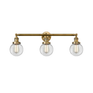 Beacon Brushed Brass Three-Light Bath Vanity with Six-Inch Clear Globe Glass