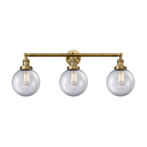 Beacon Brushed Brass Three-Light Bath Vanity with Eight-Inch Clear Globe Glass