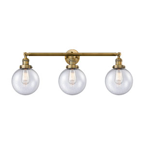 Beacon Brushed Brass Three-Light Bath Vanity with Eight-Inch Seedy Globe Glass
