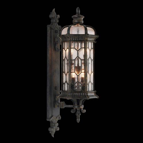 Devonshire Four-Light Outdoor Wall Mount in Antiqued Bronze Finish and Features Textured Seedy Glass Panes